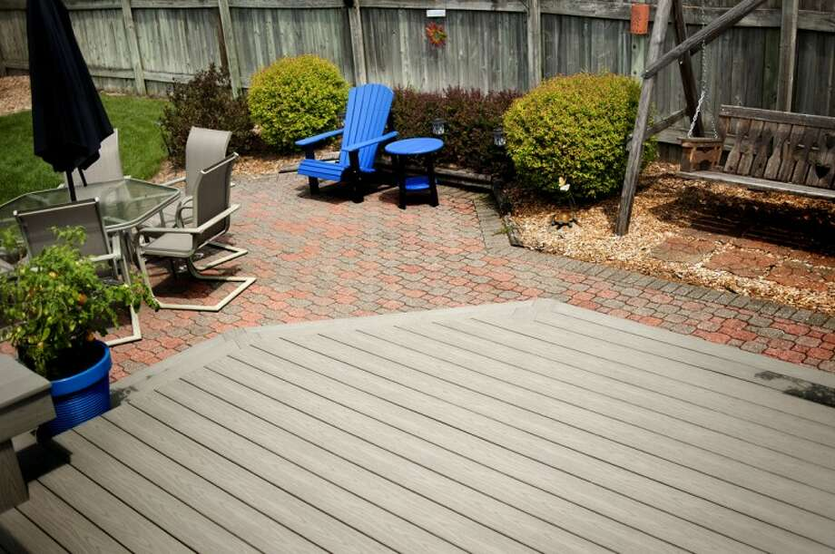 A DeWitt Lumber Co. deck recently that was recently finished in the backyard of a Midland home. The deck is made with a vinyl composite that requires less maintenance, lasts longer but is more expensive than a deck made of wood. Salesman Brain VanWert says customers are split down the middle on buying wood or composite deck. Photo: NICK KING | Nking@mdn.net