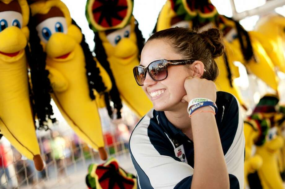 Olivia Zinser, 20, of Detroit is a game concessioner that has been traveling from town to town for county fairs for two months. She said she enjoys the job and helps pay her family's bills with the money she earns. Photo: THOMAS SIMONETTI | Tsimonetti@mdn.net