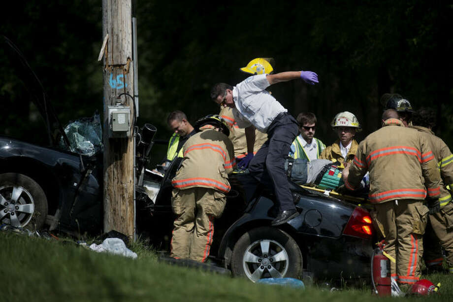 SEAN PROCTOR | sproctor@mdn.netEmergency responders pull a man out of his car after it collided with a utility pole on M-20 west of Currie Parkway. Photo: Sean Proctor/Midland  Daily News
