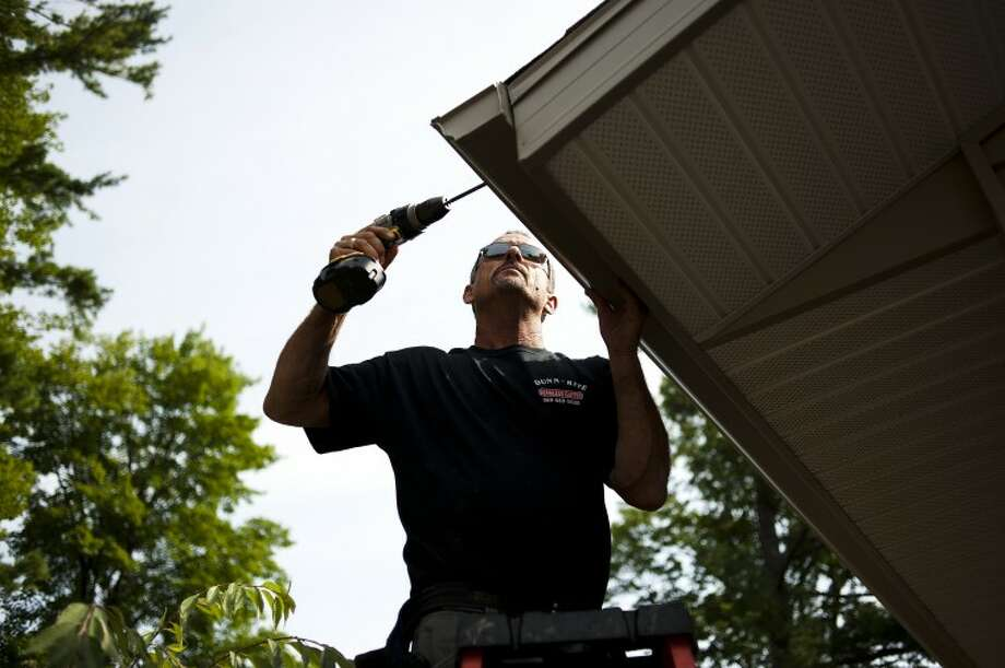 NEIL BLAKE | nblake@mdn.netLarry Stacy of Sanford with Dunn-Rite Seamless Gutters installs a gutter on a home in Sanford on Friday morning. Stacy works with his son, Rob Stacy, and together they can install a complete gutter system at several sites in a day. Photo: Neil Blake