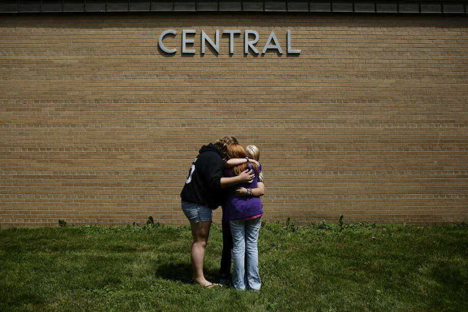 SEAN PROCTOR | sproctor@mdn.netChristine Church, Elizabeth Jerome and Brandi Porter embrace underneath the sign for Central Middle School on Wednesday after walking out of the building for the last time. Population shrinkage and declining enrollment led to the school's closure, with most students and faculty transferring to other schools in the district. Photo: Sean Proctor/Midland  Daily News
