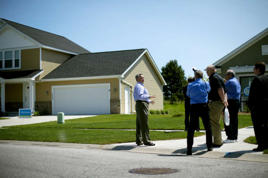 NICK KING | nking@mdn.netGary Parsons, research and development fellow, Dow Building Solutions, left, talks to members of the media about the Twelve Energy Efficiency Test Home (TEETH) project during a Dow Building Solutions tour Tuesday in Midland. Photo: Nick King/Midland  Daily News
