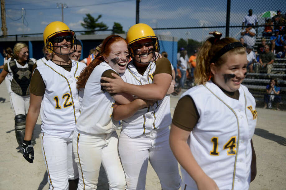 NEIL BLAKE | nblake@mdn.netBay City Western's Diondra Heading, center left, hugs Hannah Batschke, while walking back to the dugout with Ashtyn Decatur (12) and Bailey Heading (14) after their 1-0 win over Garden City in the state semifinal at Bailey Park in Battle Creek on Friday.