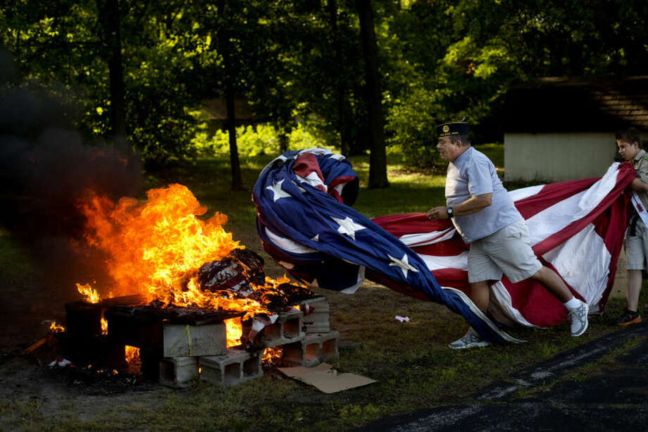 NICK KING | nking@mdn.netAmerican Legion Post 165 member Ron Lothian, center, tosses a large unserviceable flag onto a fire with the help of Boy Scout Troop 767 member Dustin Fletcher, right, during a Flag Day ceremony at the American Legion Friday in Midland.  Photo: Nick King/Midland  Daily News