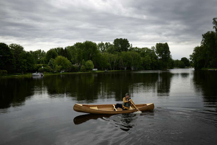 SEAN PROCTOR | sproctor@mdn.netCurt Holsinger, of Sanford, tests out his hand-built canoe on Lake Shamrock in Clare. Photo: Sean Proctor/Midland  Daily News