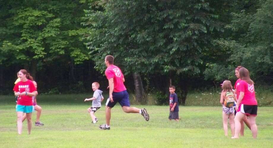 Photo providedSHARE counselor Nate Merling, center, plays soccer with day camp youthand staff.