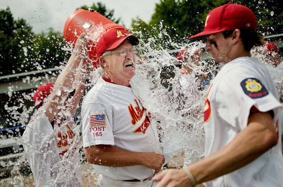 Berryhill manager Steve Cronkright is doused with water by teammates Lars Cronkright and Colton Loomis after Berryhill's 2-0 victory over Napoleon in the American Legion Great Lakes Regional Tournament championship game Monday at Gerace Stadium. Teammate Nate Kuehne, right, is hit with the water as well. Berryhill advances to the American Legion World Series, starting Friday in Shelby, N.C. Photo: NICK KING | Nking@mdn.net