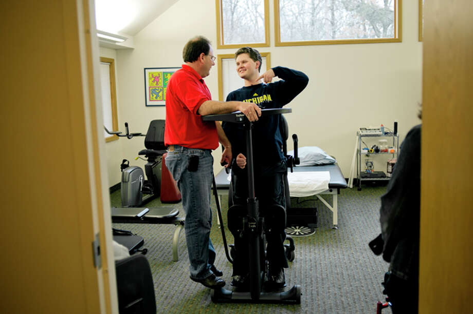 NICK KING | nking@mdn.net Occupational therapist Matt Bass, left, stands on the wheel of a piece of equipment to make himself taller while joking with James Johnson, right, during a therapy session recently at Deer Run Rehabilitation. Johnson was severely injured in a car crash in 2011, suffering traumatic lung and brain wounds. He is now recovering at Deer Run Rehabilitation, where he is receiving 24-hour care and is close to his aunt and uncle who live in Midland. Photo: Nick King/Midland  Daily News / Midland Daily News