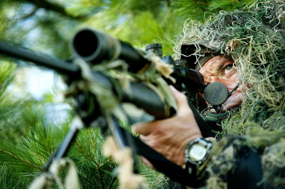 "Midland Police Department SWAT sniper John Dubois, 42, lays atop a hill in brush covered in camouflage as he practices his accuracy and eye behind the barrel and crosshairs of a Remington 700, .308-caliber sniper rifle June 28 at an off-road training facility in Midland. Dubois, who has been with Midland's SWAT for 14 years, trains once a month in team shooting exercises, but logs about three hours weekly atop his regular policing duties to keep his eye keen for sniper shooting. ""You look through the crosshairs, and that's what you focus on,"" he said. ""You've got to eliminate everything else around you, but be cognizant of it as well. Sometimes it's split-second decision making, whether you pull the trigger or not. When you pull it, you have to be 100 percent certain you know where that round will land because once you pull it, you can't get that round back."" Photo: JAKE MAY 