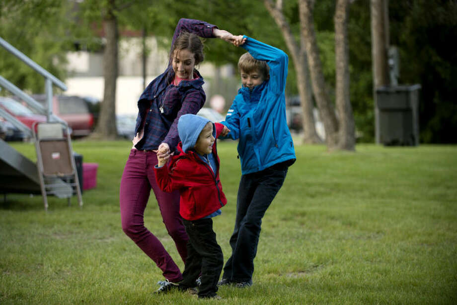 Chelsea Quinn, left, dances with Jonathon, 4, and his older brother William, 9, on Thursday during the first Tunes by the Tridge concert of the year. The free concert series continues through August. Photo: Neil Blake/Midland  Daily News