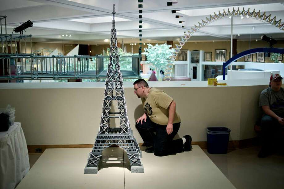 NICK KING | nking@mdn.net Scot Thompson, of Bay City, checks over the Eiffel Tower he just finished building with legos Saturday at the Midland Center for the Arts. Thompson, who is the president of the Michigan LEGO Users Group, built the Paris landmark with the help of museum guest Carol Yee in about 5 and a half hours. Thompson said that Saturday was the third time he'd live built the structure. Thompson and others from the Michigan LEGO Users Group and the Michigan LEGO Train Club have LEGO-built cities on display at the museum until September. Photo: Nick King/Midland  Daily News