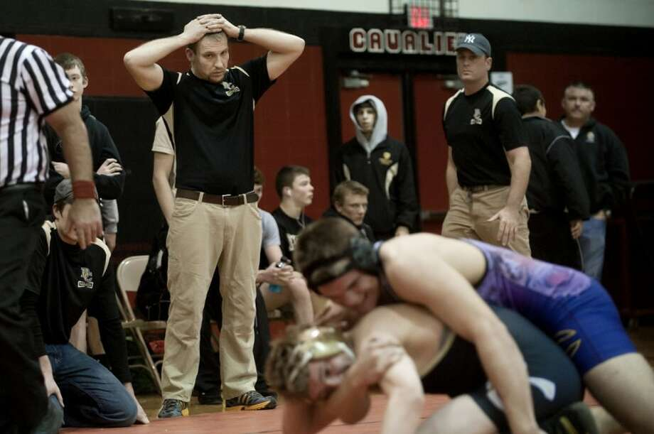 Bullock Creek coach Nick Wardell, left, looks on as Lancer Brent Pobecik wrestles with Caro's Nate Gosson during their 215-pound weigh class match during the regional meet s Wednesday at Carrollton High School. Gosson won the match. Bullock Creek lost to Caro 33-31. Photo: NICK KING | Nking@mdn.net