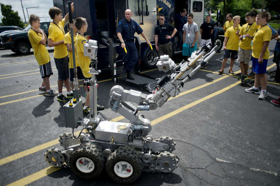 NICK KING | nking@mdn.netSgt. Rick Bekemeier, a bomb tech with the Michigan State Police, center, talks about a remote-controlled robot used in bomb investigations to members of the Midland Youth Law Enforcement Academy at the Midland Law Enforcement Center on Tuesday. Bekemeier demonstrated the robot by maneuvering it to a van in the parking lot. Photo: Nick King/Midland  Daily News