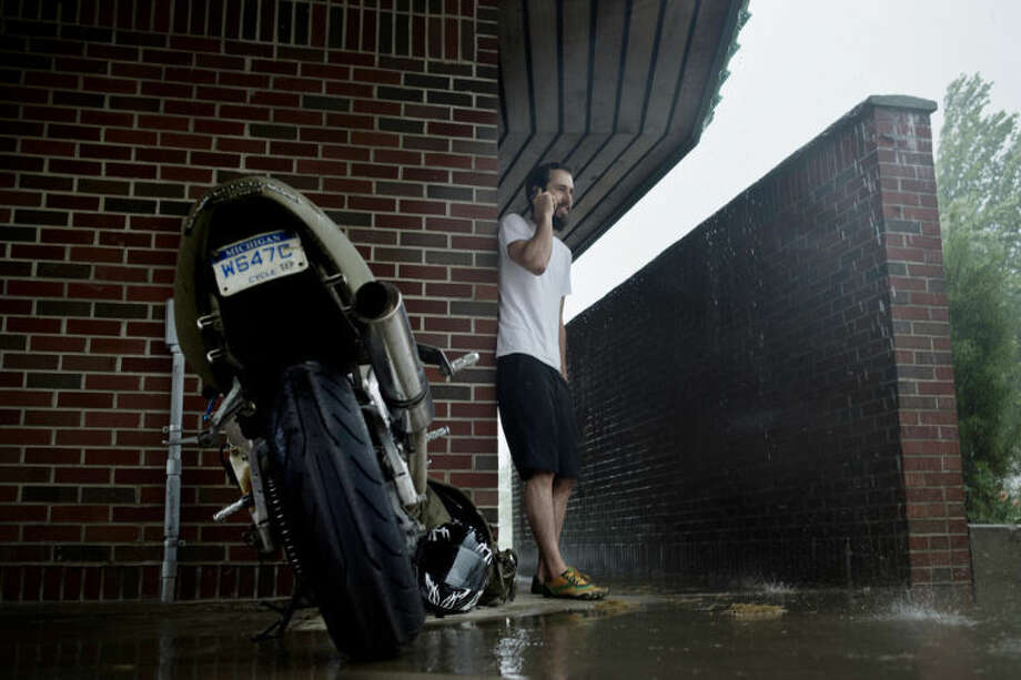 SEAN PROCTOR | sproctor@mdn.net Cody Smith, of Hemlock, stands next to his motorcycle and makes a phone call while taking shelter from the rain underneath the roof at the Farmer's Market on Monday afternoon. Smith said he had just gotten off work and planned to go for a run when the storm hit. Photo: Sean Proctor/Midland  Daily News