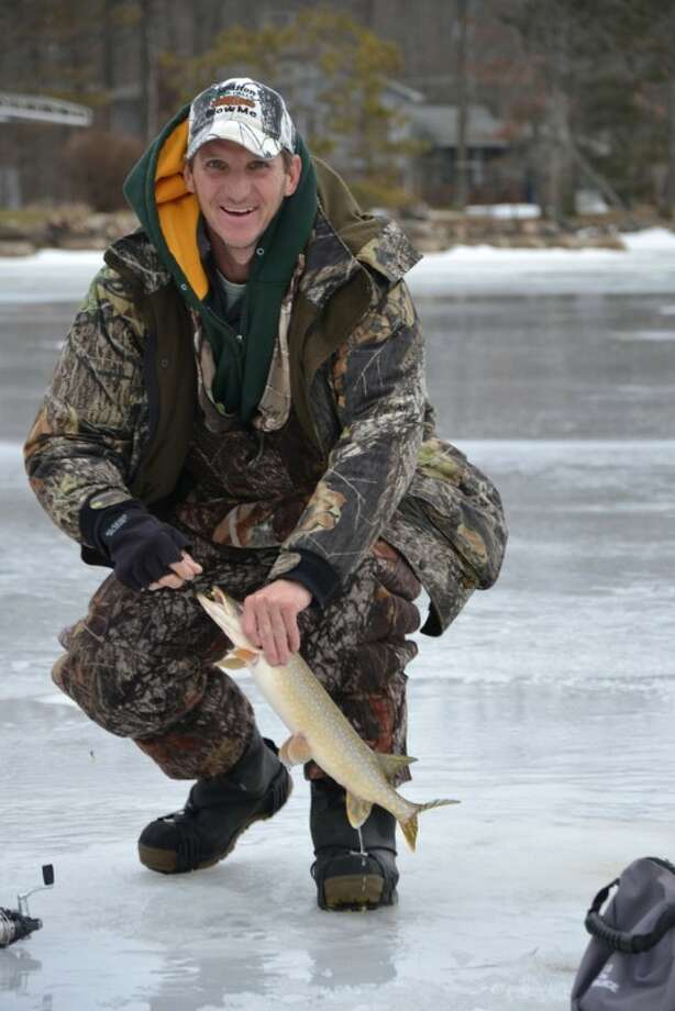 Brad Raber of Sanford and the scrappy northern pike he caught last week on Wixom Lake using gear assembled for much smaller fish.