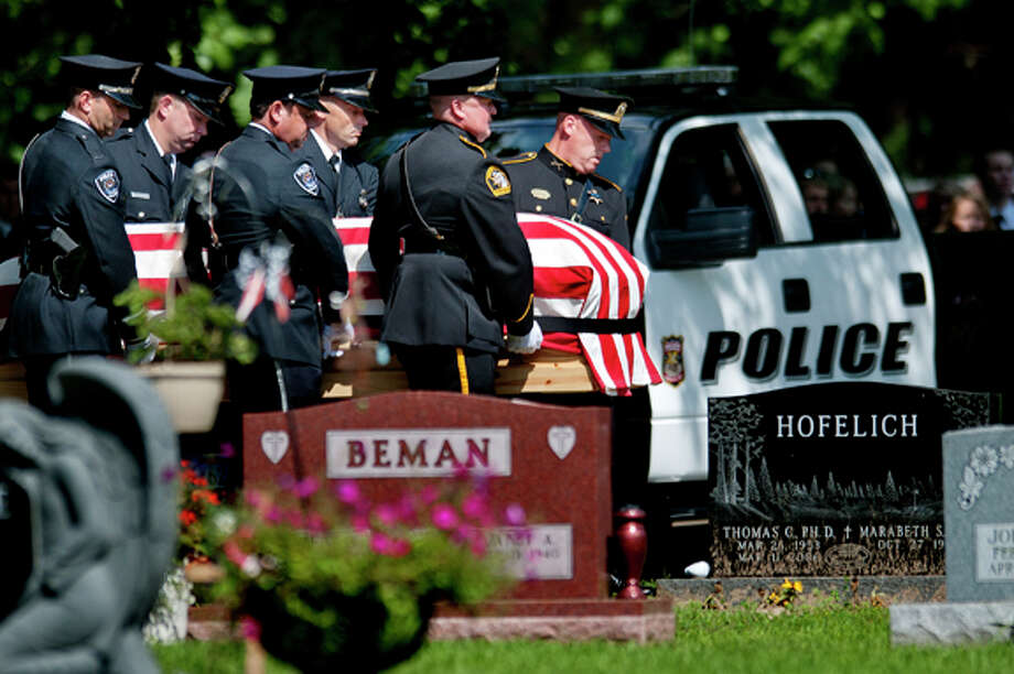 Police carry the casket of Rapid City Police Officer J. Ryan McCandless during the funeral for McCandless Thursday, Aug. 11, 2011, at the Midland Cemetery in Midland Mich. In the background is McCandless' patrol vehicle. McCandless was killed in the line of duty last week in South Dakota. McCandless, a 2001 H.H. Dow High graduate, is the son of retired Midland County Undersheriff James McCandless. Photo: NICK KING | Nking@mdn.net  / Midland Daily News