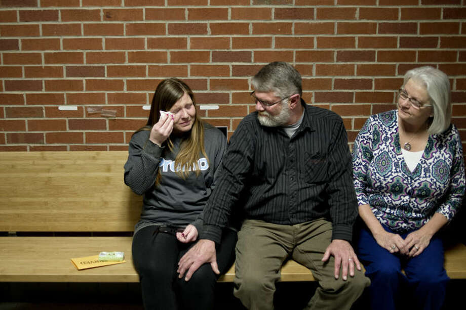 NICK KING | nking@mdn.netSarah Premo, left, is comforted by her father, Dave Premo, center, as the two and Dave's wife Joanne, right, sit on a bench dedicated to Sarah's brother, David James Premo, Thursday at Delta College. Family, friends and staff participated in the event for Delta student David Premo, who was killed in a car crash on Oct. 16, 2012. Photo: Nick King/Midland  Daily News