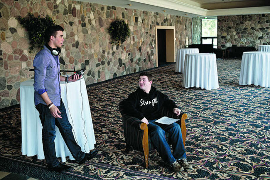 Michael Rubenstein, 20, center, a Northwood junior, looks up at Sterling Adgate, 21, also a Northwood junior, while filming a promotional video for an upcoming fundraiser event Wednesday afternoon in the lobby of the Great Hall Banquet and Convention Center. Photo: Sean Proctor/Midland  Daily News