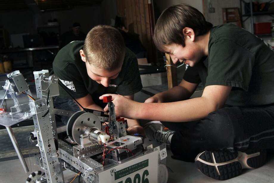 ASHLEY MILLER | for the Daily NewsNick Kopec, 12, right, laughs with his teammate, Ben Balen, 14, both of Freeland, while adjusting the position of the arm on the Freeland Fabricators' robot during team practice Sunday night. Kopec said the best part of being on the team is trying to get stuff to work.