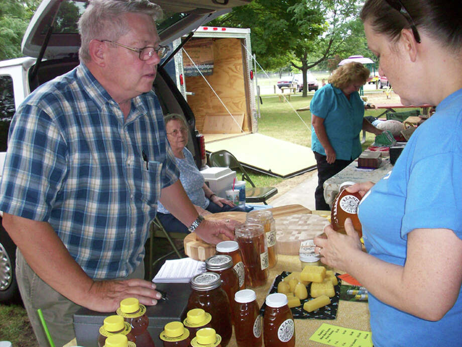 For the Daily News | Patti BrandtBrandy Smith-Symons, of Shields, right, checks out honey products sold by Dan Keane, treasurer of the Hemlock Farmers Market.