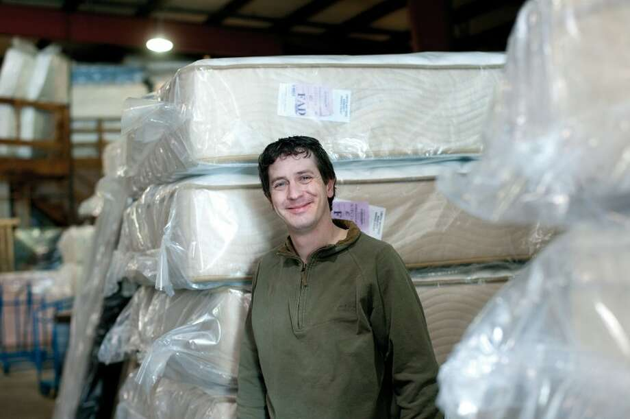NICK KING | nking@mdn.netDan Dan the Mattress Man stands in the warehouse near some of the mattresses he offers at his Midland store. Photo: Nick King/Midland  Daily News