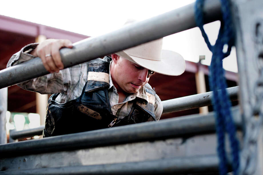 Chris Ripley of Vermontville, Mich. holds the gate before riding a bull at the Midland County Fair Championship Rodeo on Wednesday. In addition to bull riding, the night also featured bareback riding, saddle bronc riding, girl's barrel racing and team roping, Photo: THOMAS SIMONETTI | Tsimonetti@mdn.net  / Midland Daily News