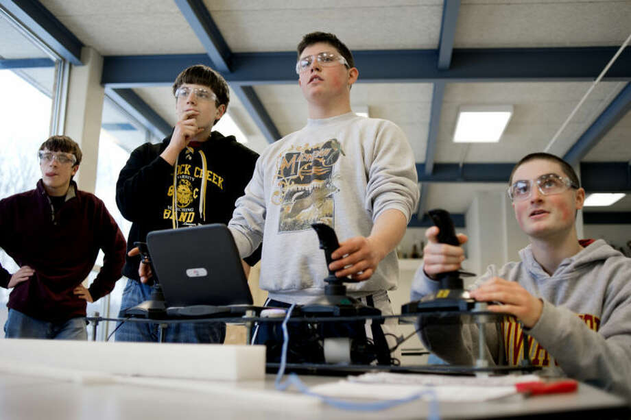 NICK KING | nking@mdn.netFrom left, Bullock Creek students Chris Eidsmoe, and his brother, Nick, look on as Tyler Miller, center, and Daniel Maak control a Frisbee-shooting robot during a BlitzCreek Robotics team practice Monday in the school cafeteria. Photo: Nick King/Midland  Daily News