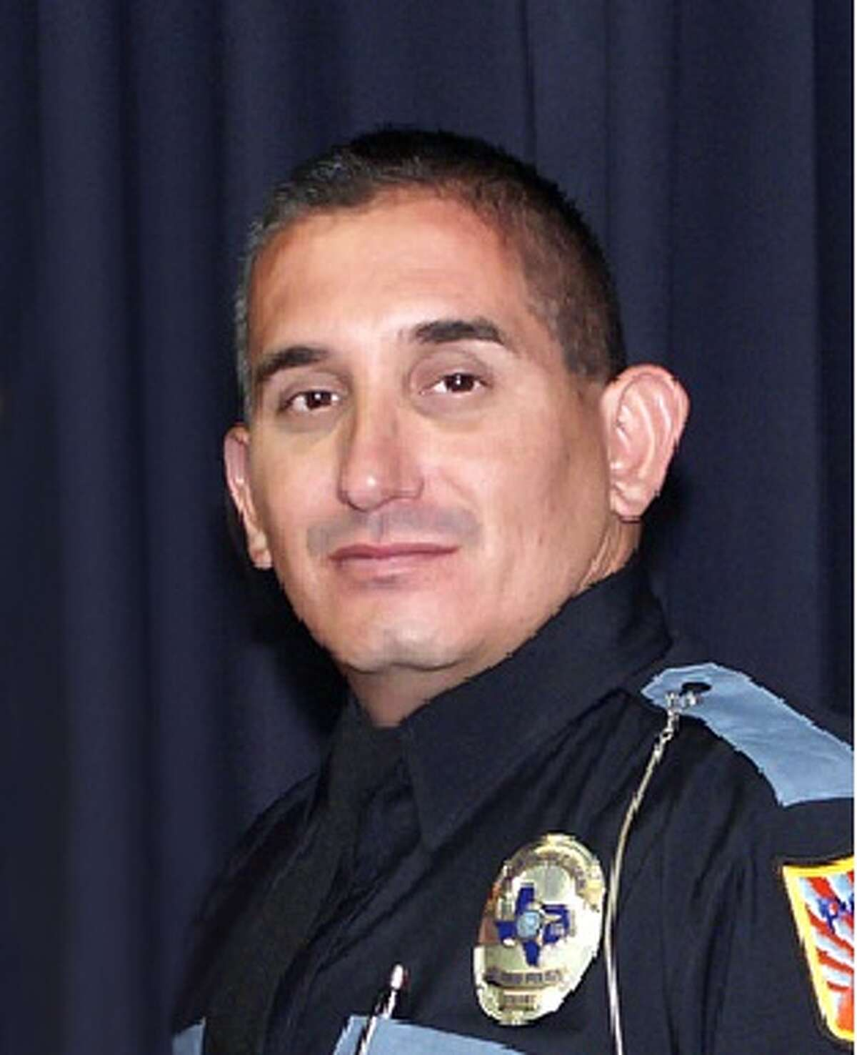 John Perry - a 45-year-old El Paso man previously accused of being a member of the Barrio Azteca gang - was behind the wheel of a Kia Optima when he hit a motorcycle driven by Officer David Ortiz (pictured) from behind on March 10, the El Paso Police Department announced Monday. Ortiz died of his injuries on March 14.
