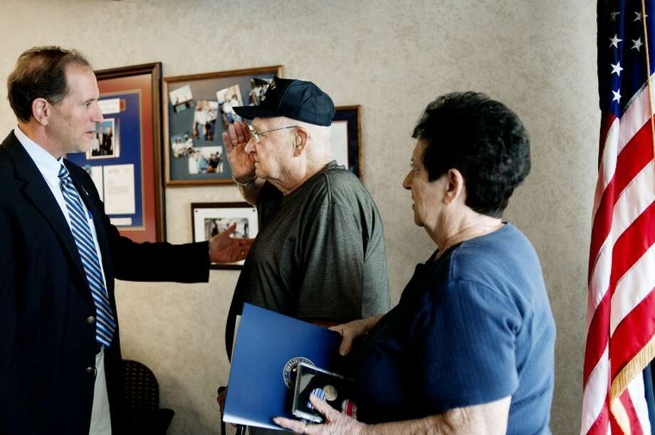 NICK KING | nking@mdn.netWorld War II Veteran Delton Miller, center, salutes U.S. Rep. Dave Camp, left, as Miller's wife, Vi, looks on after Camp presented Miller with five military medals Thursday at Camp's Midland office. Miller served in the U.S. Navy.