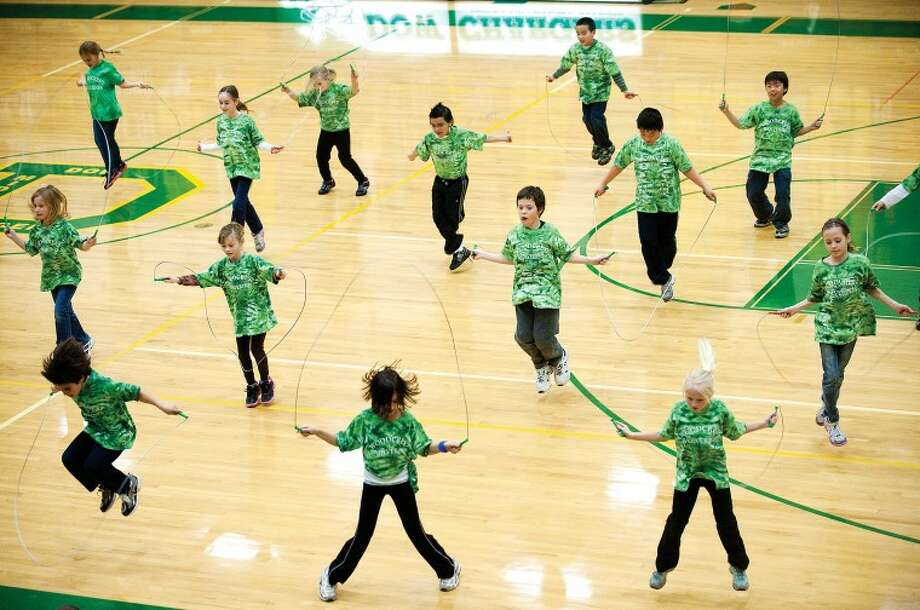 """Thirteen of more than 60 Woodcrest Elementary School students jump rope on the basketball court during half time of the Dow basketball game against Davison for the crowd Tuesday night at Dow High School. The routines, played out to different songs, were not only performed individually, but also with multiple people using the same jump ropes, and performing tricks with as many as five people in one jump with one rope. """"My advice to anyone who wants to try to jump rope ... don't mess up,"""" said Woodcrest fourth-grader Jared Poliskey of Midland, 10. """"You just have to keep working hard, keep trying and never give up. Everybody can jump rope."""" Photo: JAKE MAY 