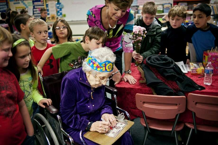 THOMAS SIMONETTI | tsimonetti@mdn.netHazel Weymouth, who is 100 years old, signs a fake $100 bill with her photo on it in Terri Dulude's second grade class at Chestnut Hill Elementary School in Midland on Wednesday. Weymouth was invited to speak to the class to celebrate the 100th day of the school year, which is today. Photo: Thomas Simonetti