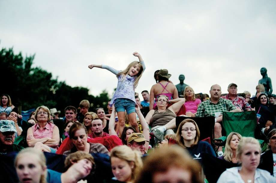 Emmie Pratt, 6, dances to the music during the Montgomery Gentry concert Sunday at Chippewassee Park. Emmie's mother, Mindy, held her daughter on her shoulders for a better view of the concert that brought hundreds to Chippewassee Park. Photo: NICK KING | Nking@mdn.net