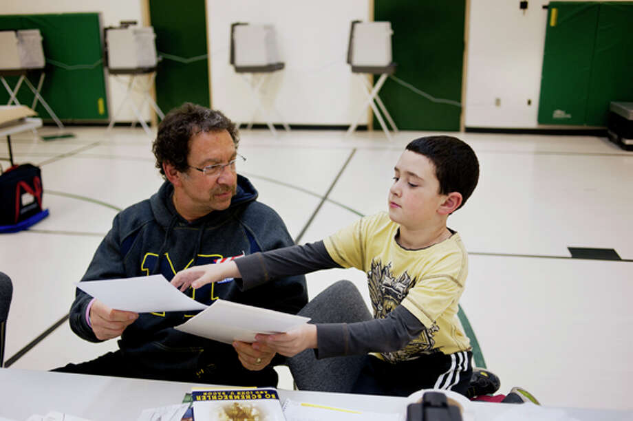 Rick Bergstein of Midland hands his grandson, Ethan, 7, a ballot to put together before giving it to a voter at Woodcrest Elementary on Tuesday. Ethan has worked with his grandfather in prior elections and says that he enjoys helping out. Rick has volunteered for the past five years. Photo: NEIL BLAKE | Nblake@mdn.net / Midland Daily News
