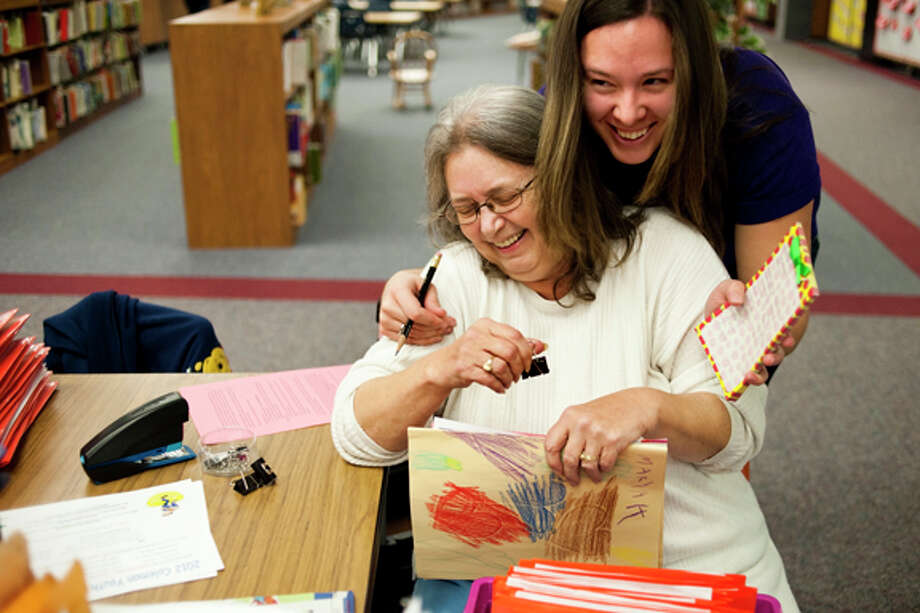 """Diane Burwick, of Coleman, center, smiles as kindergarten teacher Nicole Howdyshell, of Clare, gives her a hug for helping sort through homework and other notes for all of the elementary school teachers into file folders for classes Friday morning at Coleman Elementary School. Burwick has volunteered at the school for about 12 years, making all of the copies for teachers, as well as helping with programs with students throughout the year. """"We can spend less time on copies and sorting through papers and more time with classroom activities and all of the children because Diane does so much for each teacher here,"""" Howdyshell said. Photo: JAKE MAY 