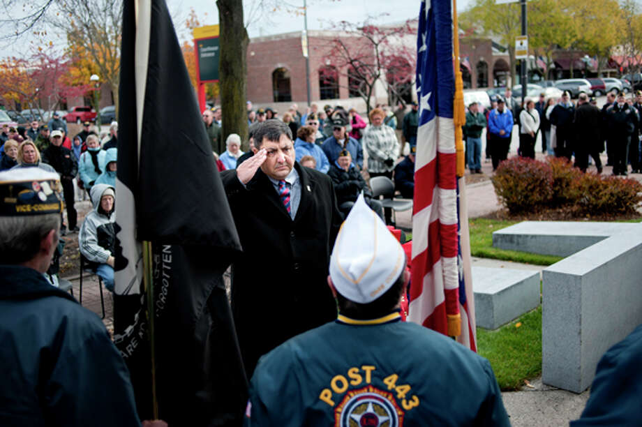 State Rep. Jim Stamas salutes the flag before placing a wreath at the war memorial Friday during a Veterans Day ceremony outside the Midland County Courthouse. Stamas served in the U.S. Army and the Michigan National Guard. The ceremony included a keynote address from Congressman Dave Camp, a prayer, the playing of taps and a 21-gun salute. Honor guards from the VFW Post 3651, American Legion Posts 165 and 443, AMVETS 3652 and the Disabled American Veterans 94 participated in the ceremony. Photo: NICK KING | Nking@mdn.net  / Midland Daily News