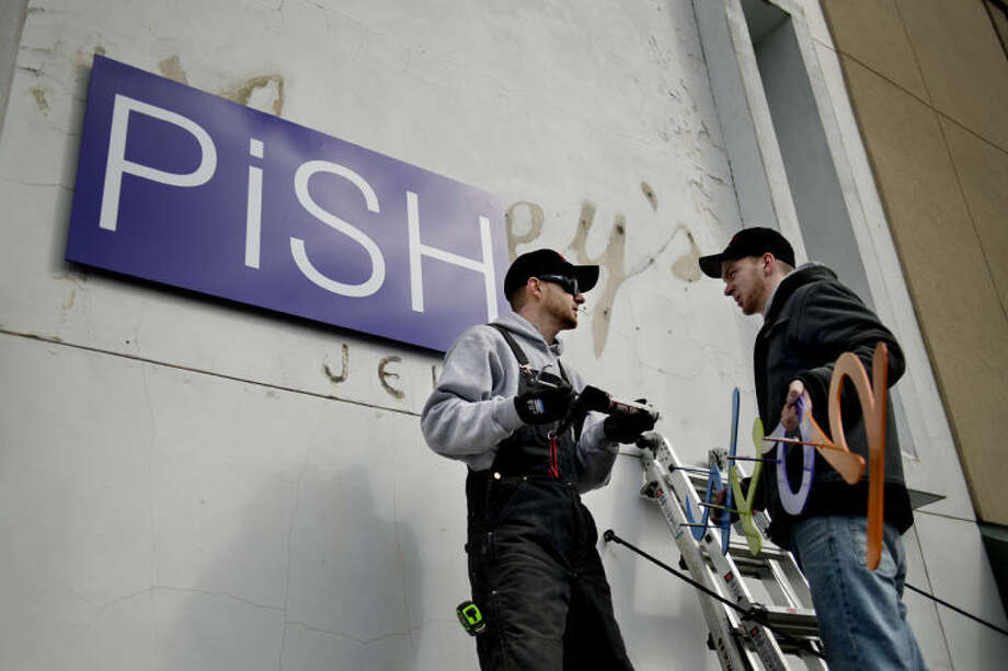 "NEIL BLAKE | nblake@mdn.netCory Kintner, left, and Jon Samuel of High Image Design install the sign for ""Pish Posh,"" a baby boutique store that has moved to downtown Midland. Photo: Neil Blake/Midland  Daily News"