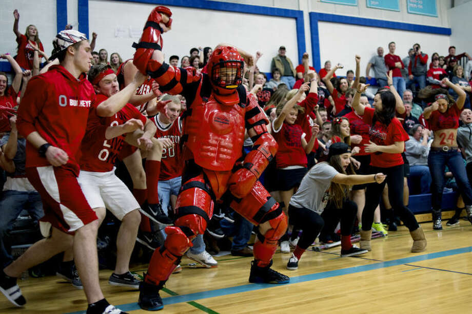 NICK KING | nking@mdn.netWearing full-body protection pads, Gladwin High School senior Michael Fennell, right, dances with the Beaverton student section during halftime of the Beavers' Class C regional semifinal game against Morley-Stanwood Monday at Meridian High School. Fennell came to the game to show support for his neighboring town. Beaverton won 60-45 and will play in the Class C regional final on Wednesday. Photo: Nick King/Midland  Daily News
