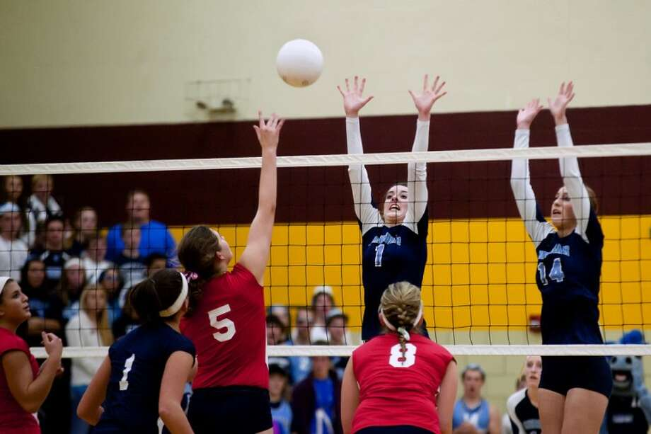 Meridian's Bri Yaroch jumps to block a hit by Miranda Fuerst of Unionville-Sebewaing during the Class C volleyball regional semifinals Tuesday night at Reese High School. At right is Meridian's Sadie Hall (14). Photo: SARA WINKLER | For The Daily News
