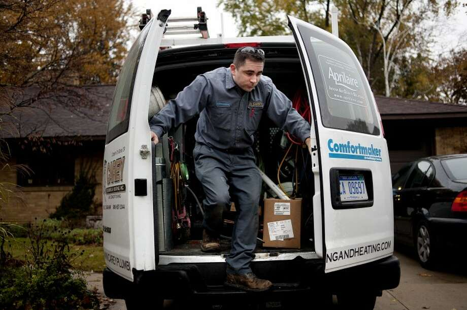 NICK KING | nking@mdn.netCarey Plumbing employee Nick Almond steps out of the company van while retrieving a part to aid in the installation of a new dishwasher at a Midland home on Thursday. Photo: Nick King/Midland Daily News
