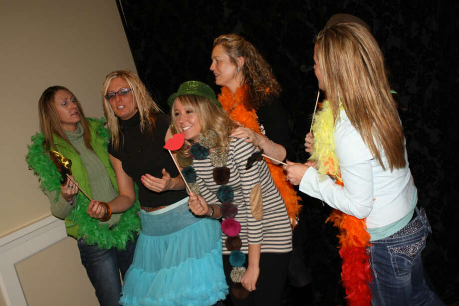 "Abby McGuire | for the Daily NewsEmployees from Hale and Hale Dentistry play dress-up with props from the photo booth provided by Captured Photography at a fundraiser for Sisters by Heart, a nonprofit organization that started in Midland. The group provides care packages to families with children with a rare congenital heart defect.  The group came to ""Ladies Night Out"" at the Midland Country Club to celebrate their belated office Christmas party.  From left are Darla Lambert, Heidi Manley, Meg Stall, Liz Fisher and Kayla Goodwin."