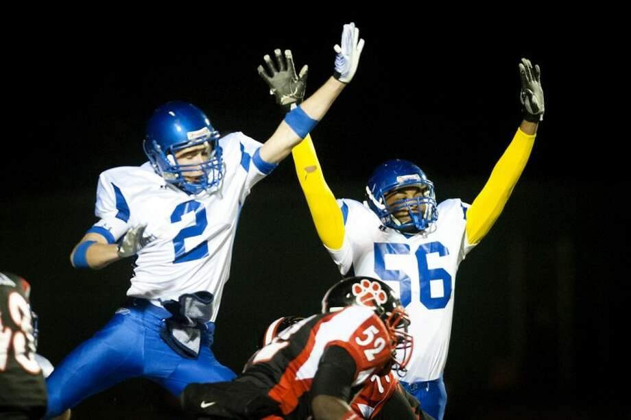 THOMAS SIMONETTI | tsimonetti@mdn.netMidland's Alec Moulton, left, and Terrence Thomas try to block an extra point in the first quarter of Friday night's district final game at Grand Blanc.