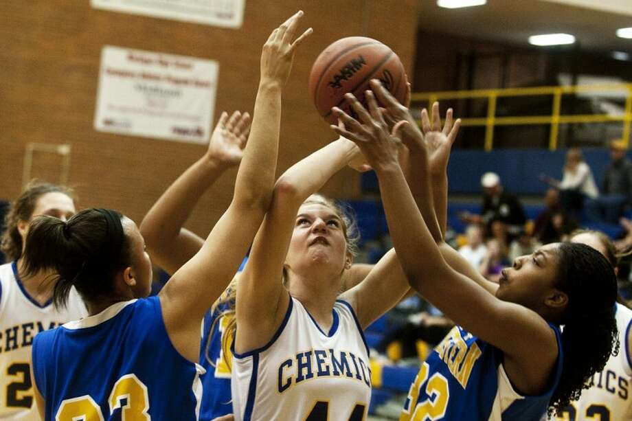 Midland High junior Leah Grinwis struggles to fend off Flint Southwestern at the basket on Friday, February 10, 2012 at Midland High School. Photo: LIBBY MARCH | For The Daily News