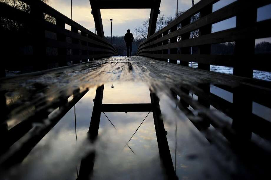 Greg Martin of Saginaw walks on the Tridge in Midland as the sun sets Wednesday. Martin said he was trying to clear his head before an online test as he works toward a Doctorate in environmental science. Photo: THOMAS SIMONETTI | Tsimonetti@mdn.net