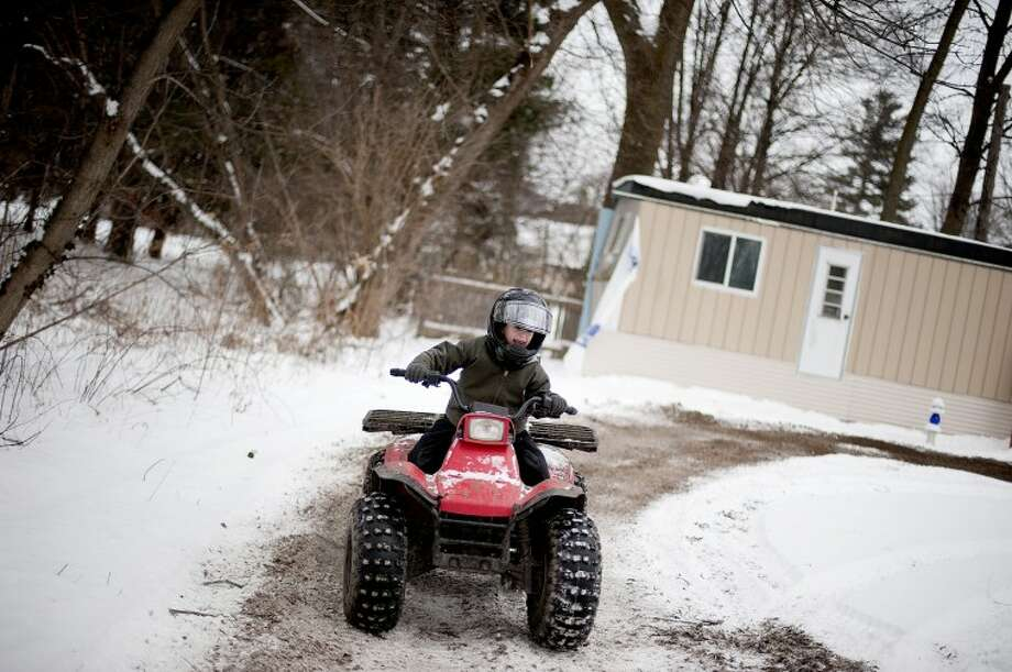 "Mixing snow with dirt, Carl Parsons Jr., 7, does doughnuts in the front yard of his home in Sanford on Saturday. Parsons, who has been riding since he was 4-years-old, received his quad, a Kawasaki 185, as a Christmas present from his parents. Since then Parsons has been riding circles in the family's yard every chance he gets. ""He told me yesterday when he was doin' doughnuts that he thought he was gonna barf,"" said Parson's mother, Amber Mosher. Photo: NATHAN MORGAN 