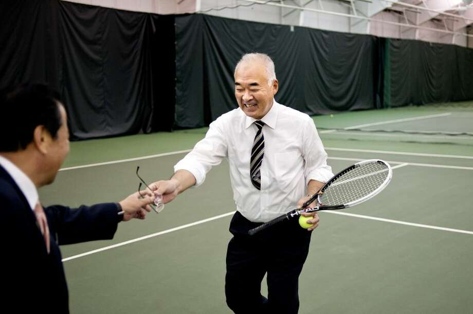NICK KING | nking@mdn.netHanda City Mayor Sumio Sakakibara, right, passes his glasses to Handa City Council Chairman Nobuyuki Sakakibara before playing tennis with Midland Tennis Center Executive Director Mike Woody during a tour of the facility as part of the 30th anniversary celebration of the Handa/Midland sister city relationship Tuesday. Photo: Nick King/Midland  Daily News