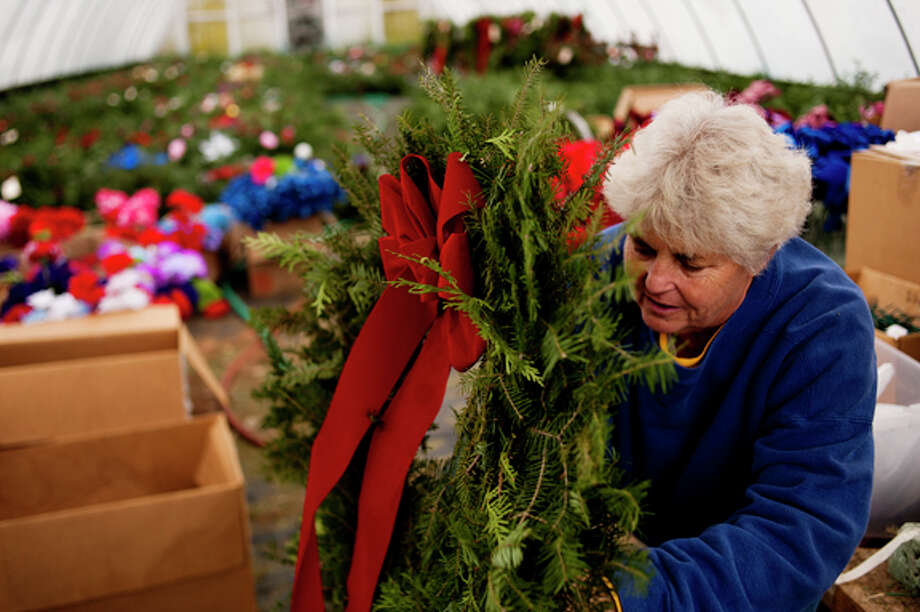 Kathy Forbes of Midland decorates wreaths for grave sites at Roy Kutchey Greenhouses in Midland on Tuesday. Wreath production is in full swing at the greenhouse and an order of 1200 wreathes for the Boy Scouts to sell was shipped out this week. Photo: NEIL BLAKE | Nblake@mdn.net  / Midland Daily News Neil Blake