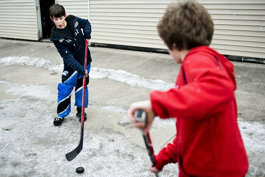 "JAKE MAY | for the Daily News Collin Carter, 12, of Memphis, Tenn., left, makes a face as he passes the puck to Cole Smallwood, 11, of Memphis, Tenn., as the two practice puck-handling skills on a patch of ice on the sidewalk on E. Railway Road near the Coleman Area Library while visiting Smallwood's grandmother Mary Simon, a Coleman resident, for his first winter visit to Michigan. Smallwood loves the Detroit Red Wings, spouting off that his favorite player in the NHL is Pavel Datsyuk. ""I was hoping to play ice hockey more, but roller hockey is fine too,"" Smallwood said. ""It's just an awesome sport. There's contact. They fight. It's really cool."" Photo: JAKE MAY 