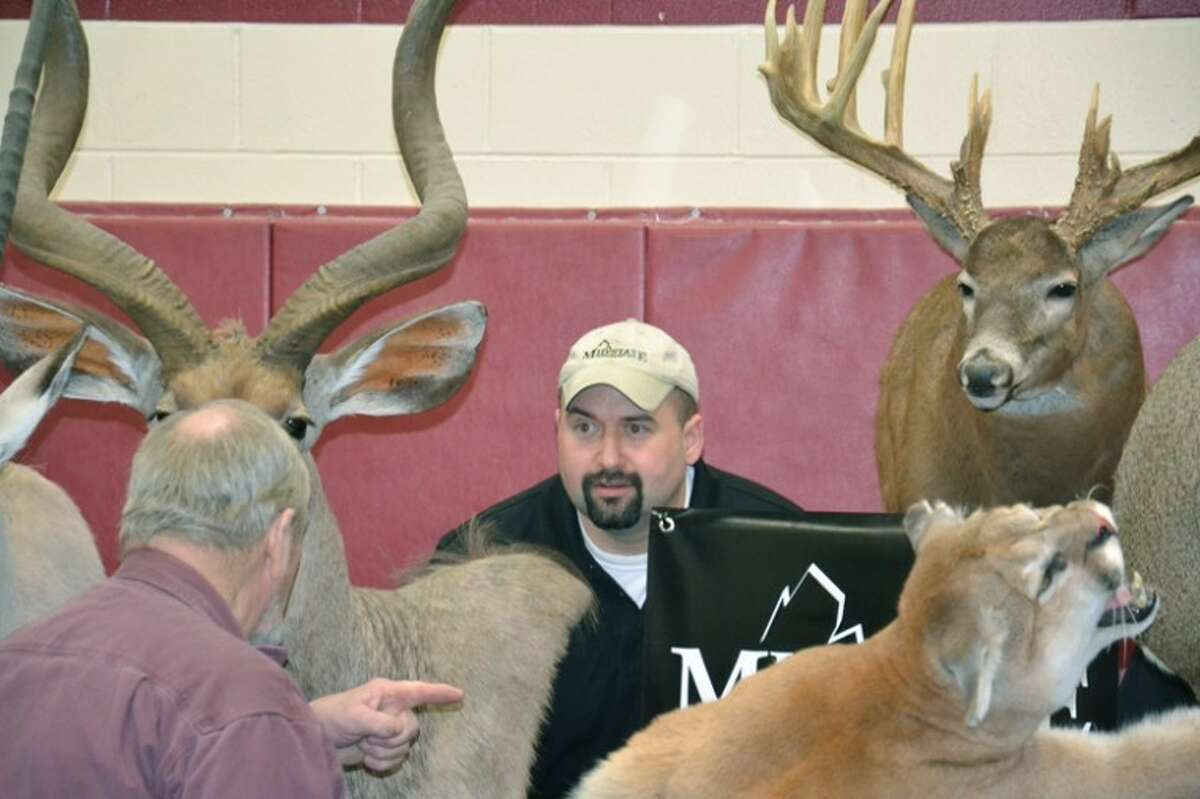 Steve Griffin   for the Daily NewsMidland taxidermist Justin Pohl, owner of Mid-State Taxidermy, is framed by some of his animal mounts at the Call of the Wild event last week.