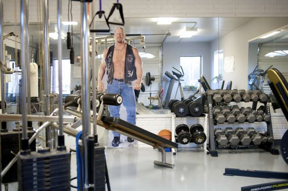 "A cutout of ""Stone Cold"" Steve Austin adorns the a wall in an exercise room built by Orvosh Builders. The room has space for free weights as well as treadmills and cycling machines. Photo: NEIL BLAKE 