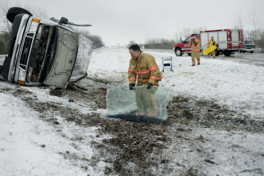Midland Fire Department firefighter Tim Longlet picks up the windshield from a passenger van while cleaning up the scene after the van rolled in the median on Business US-10 near Waldo Road. The rollover occurred Saturday morning and many of the van's passengers were sent to the hospital by ambulance. Photo: Neil Blake/Midland  Daily News